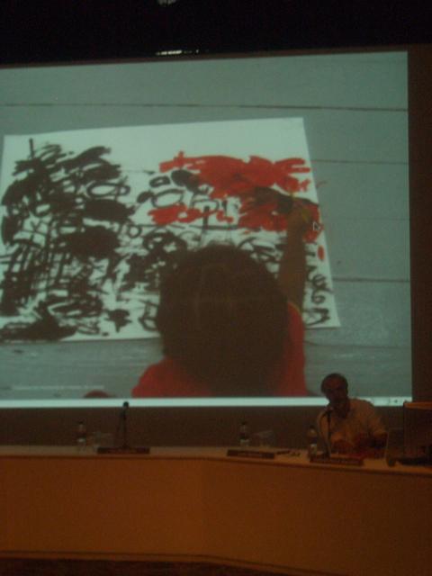 Fernando Alvim falando na frente de uma imagem sobre o programa educativo da Trienal de Luanda